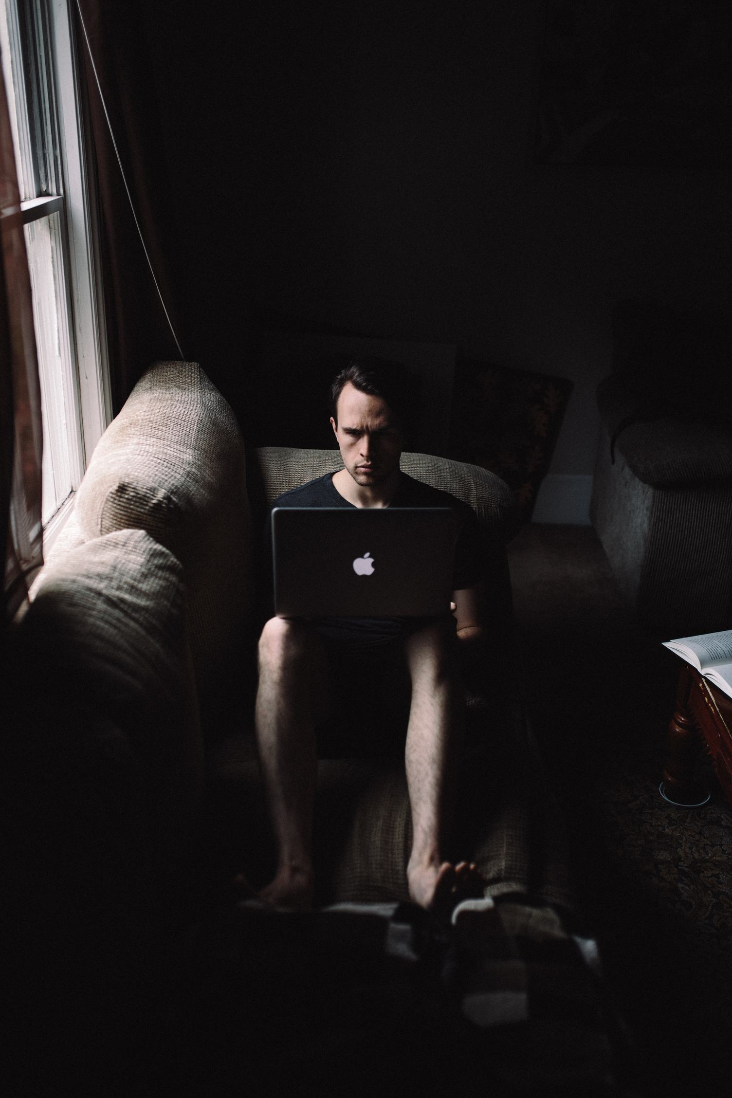Man Working on his Laptop on the Sofa at Home