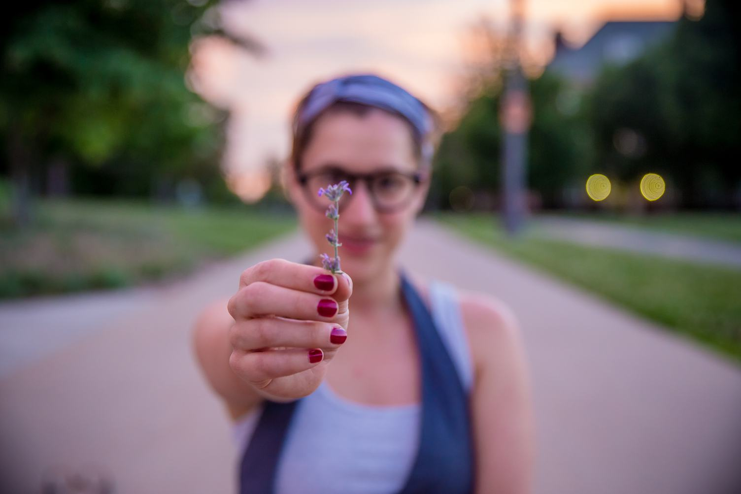 Girl with Red Nail Polish Holding a Single Flower