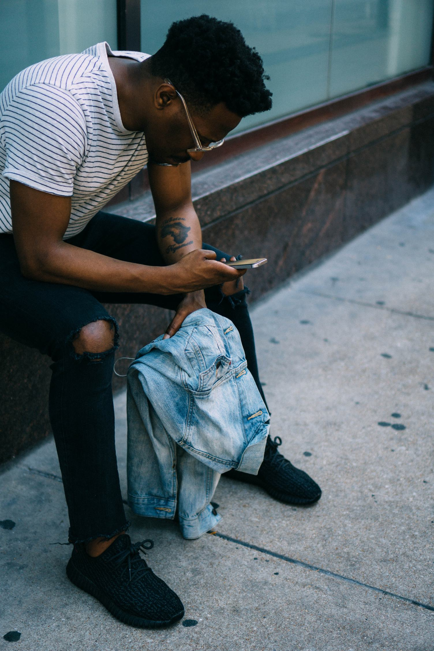 Man Holding his iPhone Wearing Black Ripped Knee Jeans