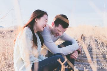 Couple Sitting and Laughing on a Railroad Tracks
