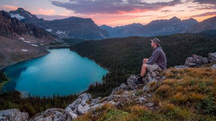 A Man Sitting on the Rock Looking at the Mountains