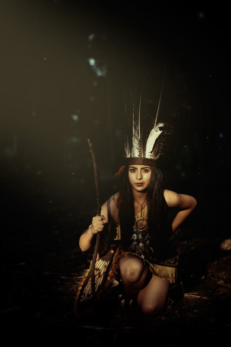 Native American Woman Wearing Plume Holding a Stick