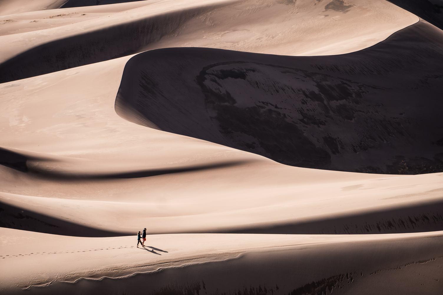 Couple Walking Through the Sand Dunes