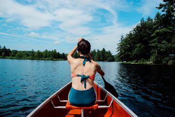 Young Brunette Girl Wearing Bikini and Sitting in a Kayak on a Lake