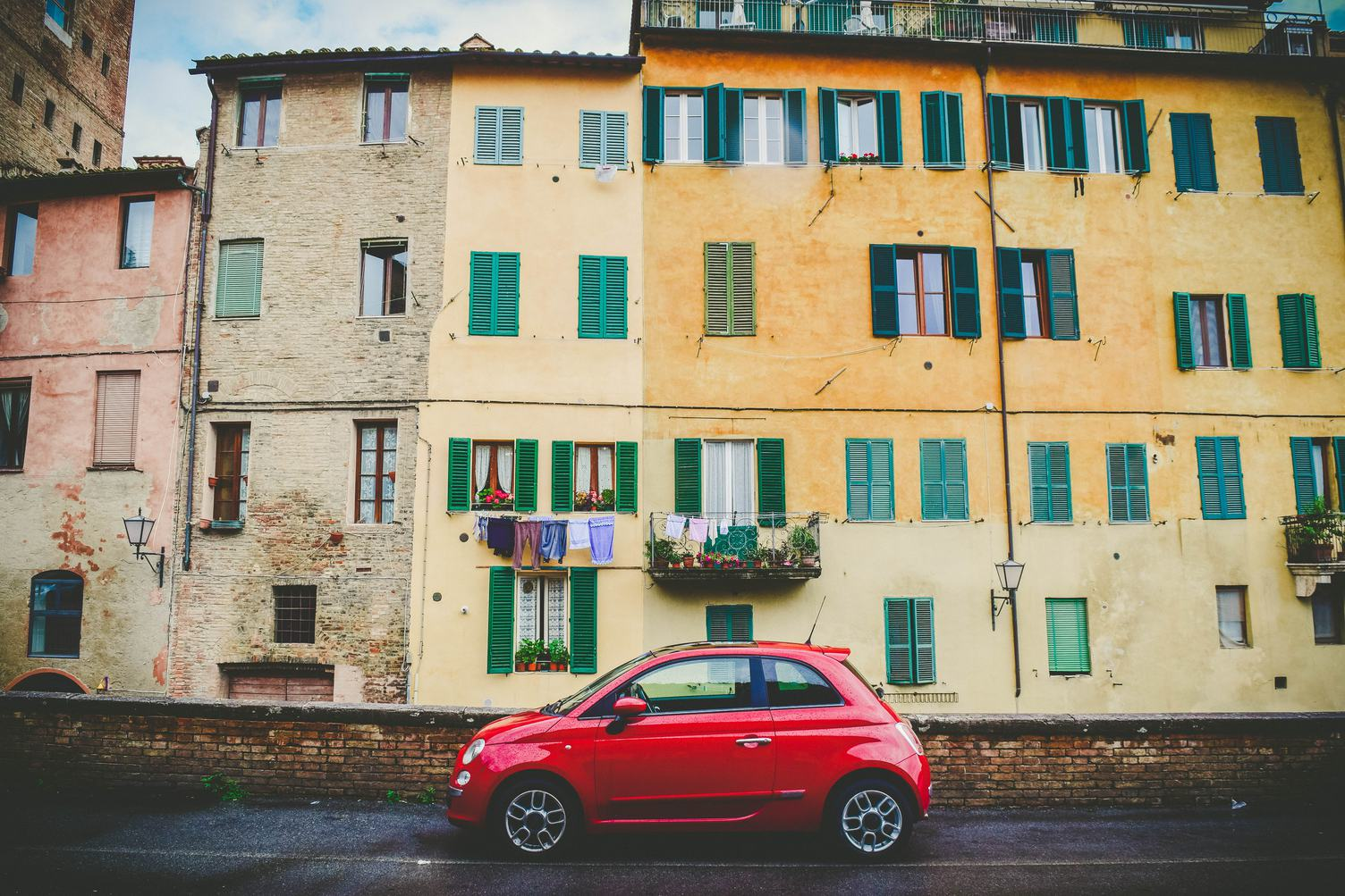Red Fiat 500 Parks in front of Old Yellow Buildings with Green Shutters in Siena Italy