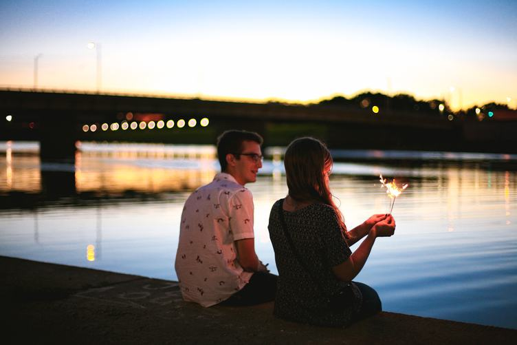 Couple of Young People Sitting on the Dock Against a Blurred Background