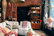 A Cozy Room with a Brick Wall and a Gray Sofa