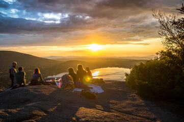 Sunset in the Mountains - Group of People Sitting with Beautiful View of Lake
