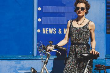 A Woman standing in Front of the Blue, Vintage Wall, Holding a City Bicycle