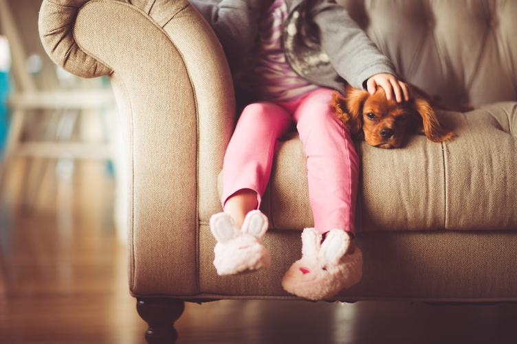 Small Girl Sitting with her Dog on a Sofa