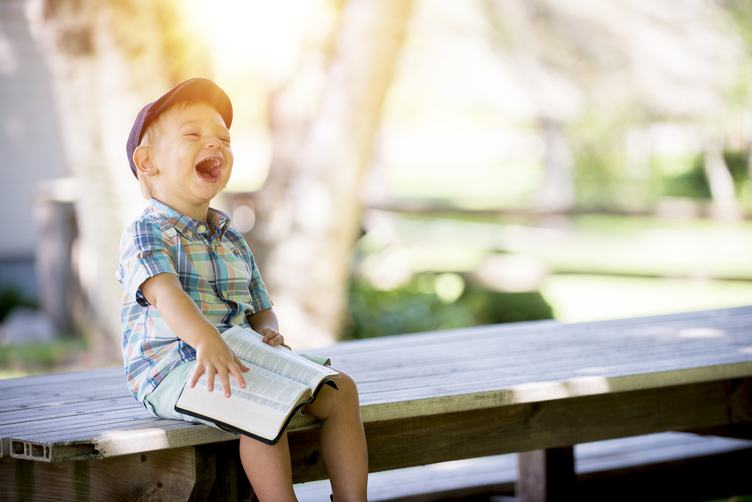 Boy Sitting on Bench and Laughing Against Light Blurry Background