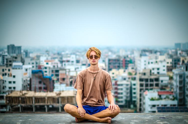Young Barefoot Man Sitting on Roof Against Blurry City Space