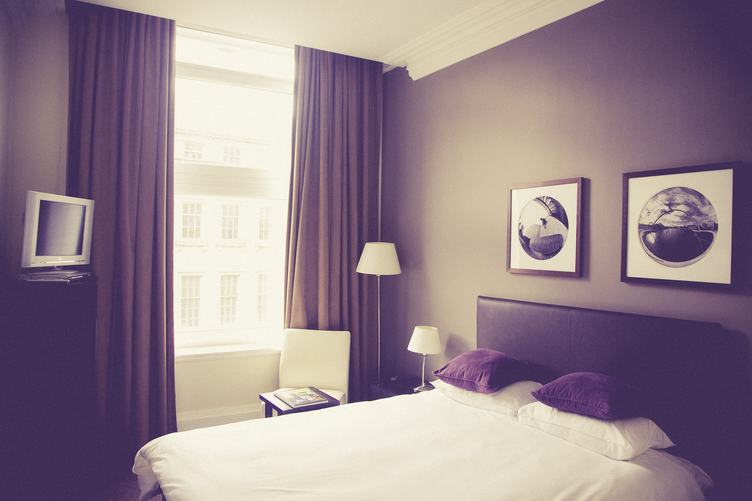 Clean Double Hotel Room with TV and Brown Curtains