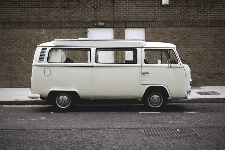 A White Volkswagen Minibus Parked in Front of Brick Wall