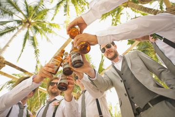 Men Drinking Beer under the Palmtrees During the Wedding Party