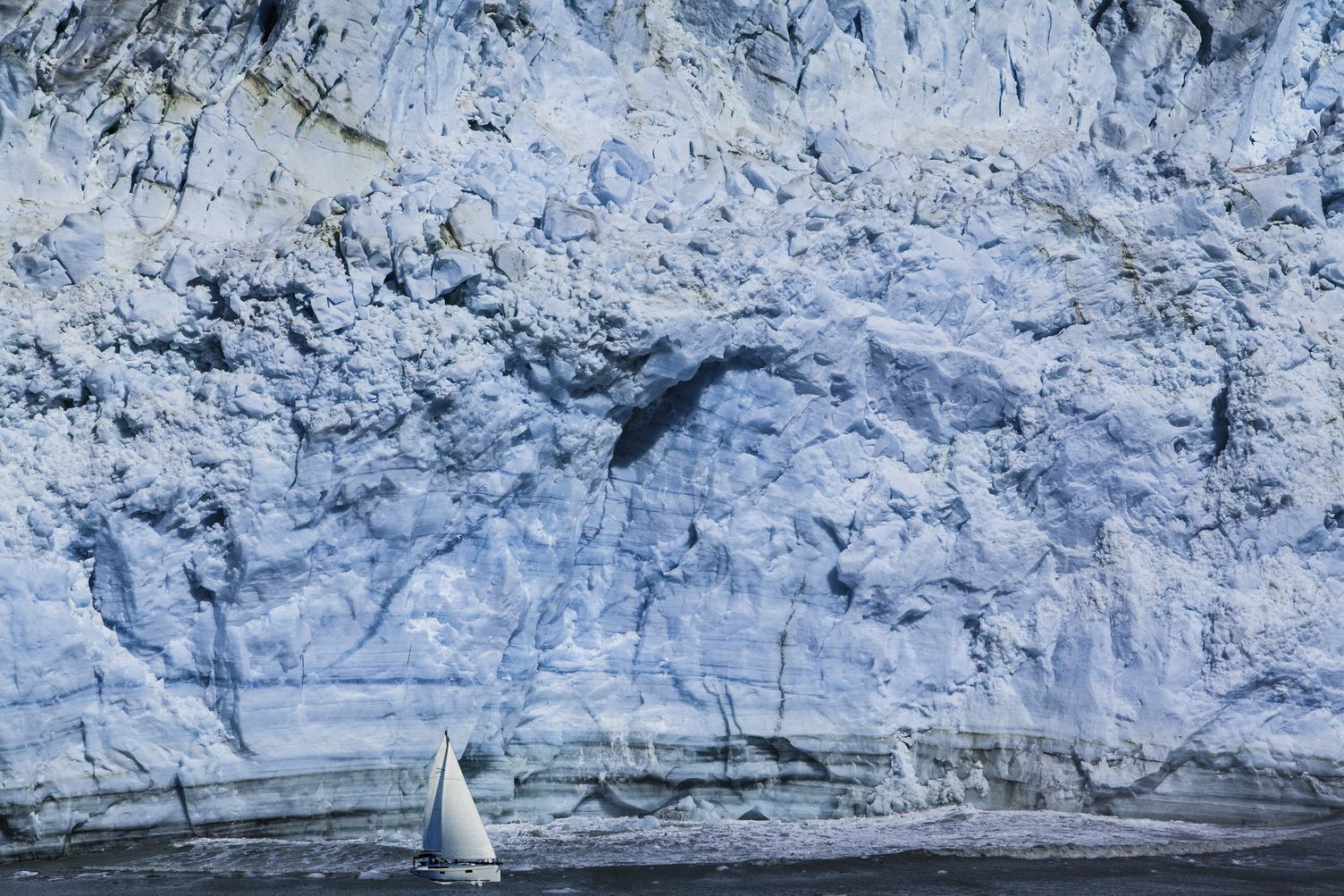 Small Sailboat against a Huge Blue Iceberg