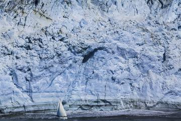 Small Sailboat against a Huge Blue Iceberg