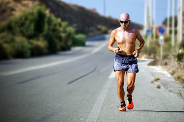 Bald Tanned Man with Sunglasses Jogging During a Hot Day
