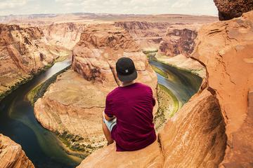 Man Sitting on the Precipice Looking on Horseshoe Bend Valley in Arisona
