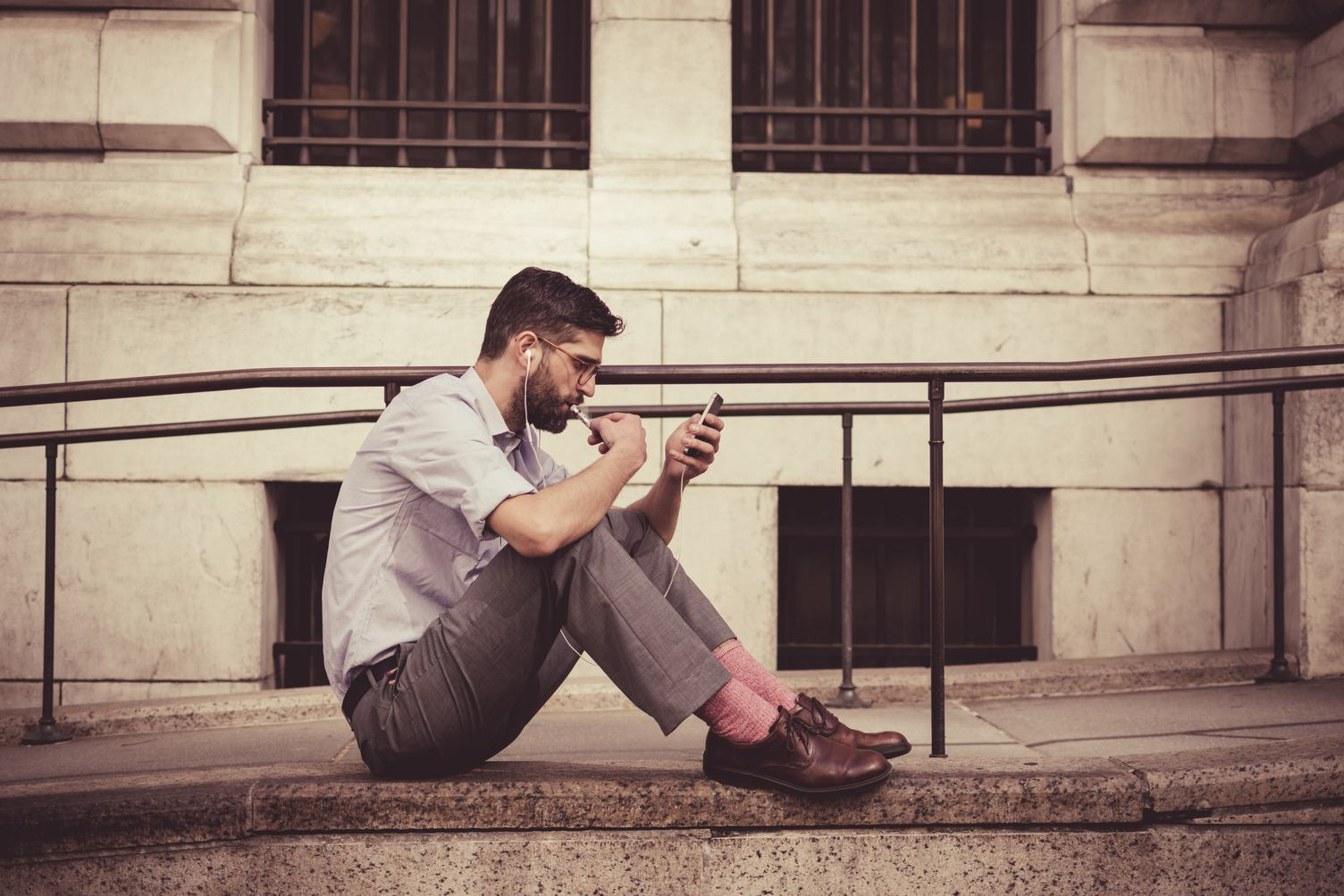 Man Sitting on the Floor in Front of a Building