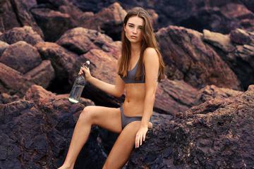 Beautiful Girl in Bikini Sitting on the Rock Holding a Bottle of Water