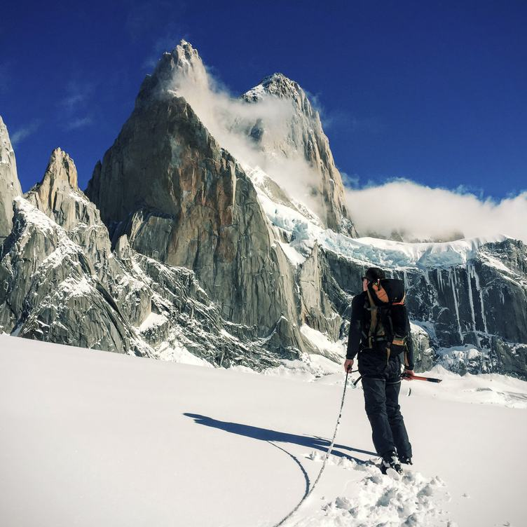 Man Standing in front of Snow Covered Mountain Peak