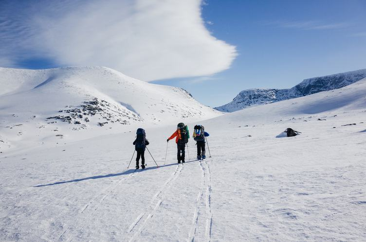 Three People Walking over Snowy Valley with Backpacks