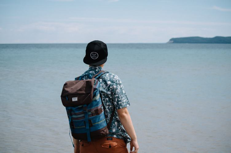 A Man with a Backpack Standing and Looking out Over a Calm Ocean