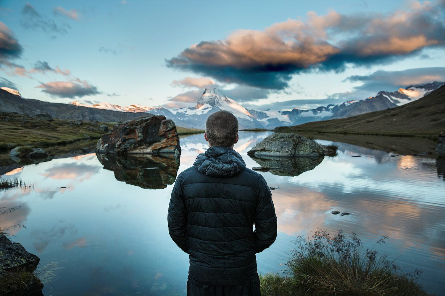 Man Standing and Looking on Peaks Reflecting in Mountain Lake