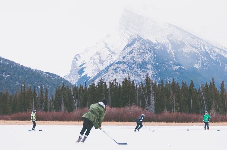 Kids Playing Outdoor Hockey at the Foot of the Mountain