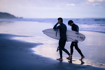 Two Men Carrying Surfing Board at the End of Day