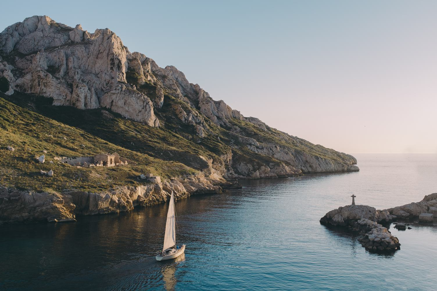 Sailing Boat In The Rocky Bay