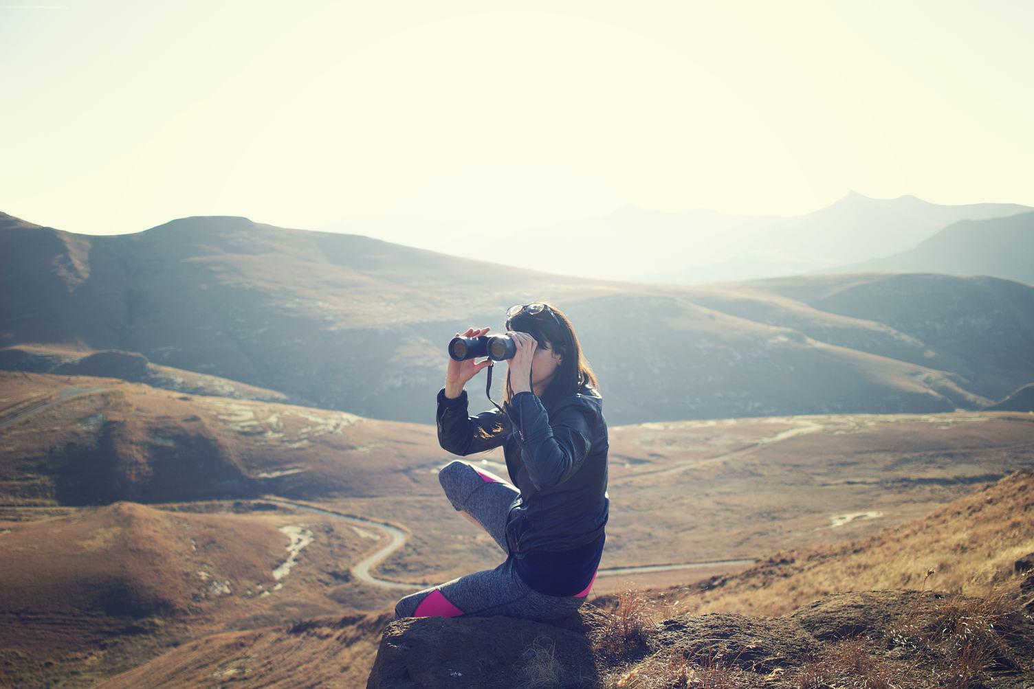 Girl Looking through Binoculars in the Mountains