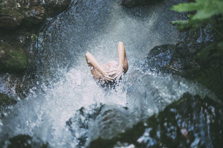 Woman Taking a Bath in the Waterfall