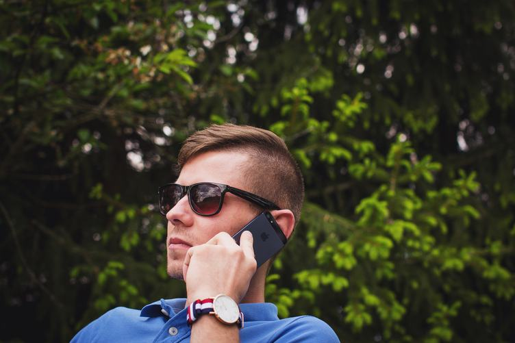 Young Man Wearing Sunglasses Talking on the Phone