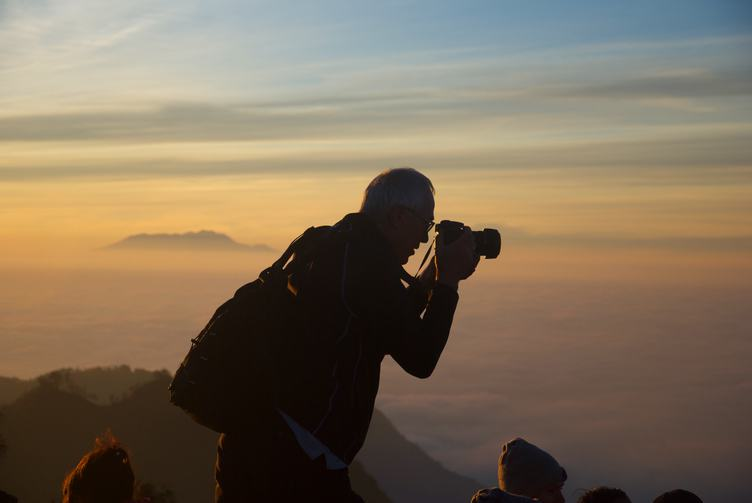 Elder Man Takes a Photo Misty Valley from Mountain Peak
