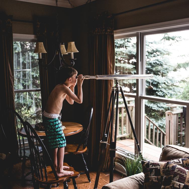 A Young Boy Observing the Nature Through a Telescope from Indoors