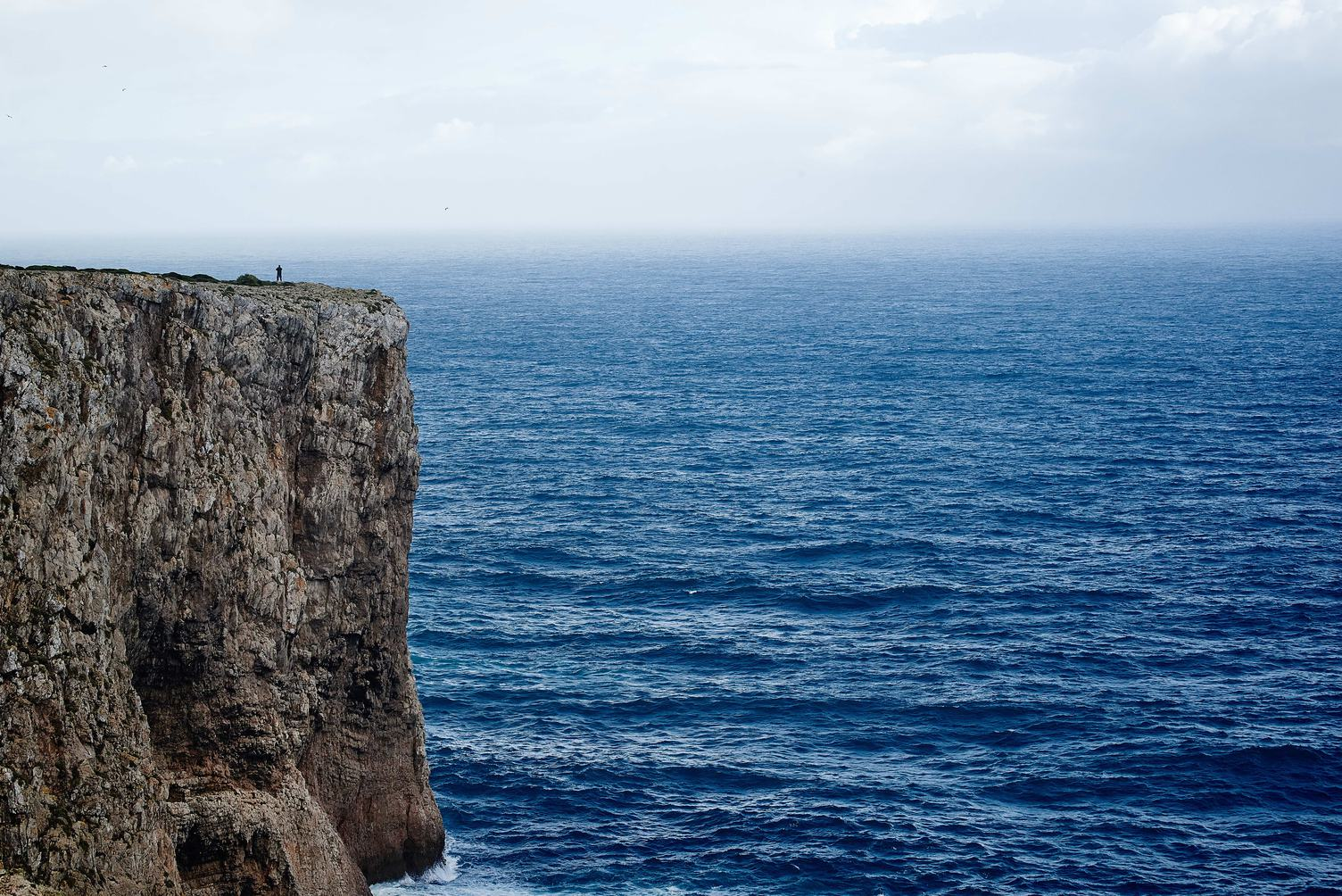 Solitary Person Standing at the Top of a Cliff