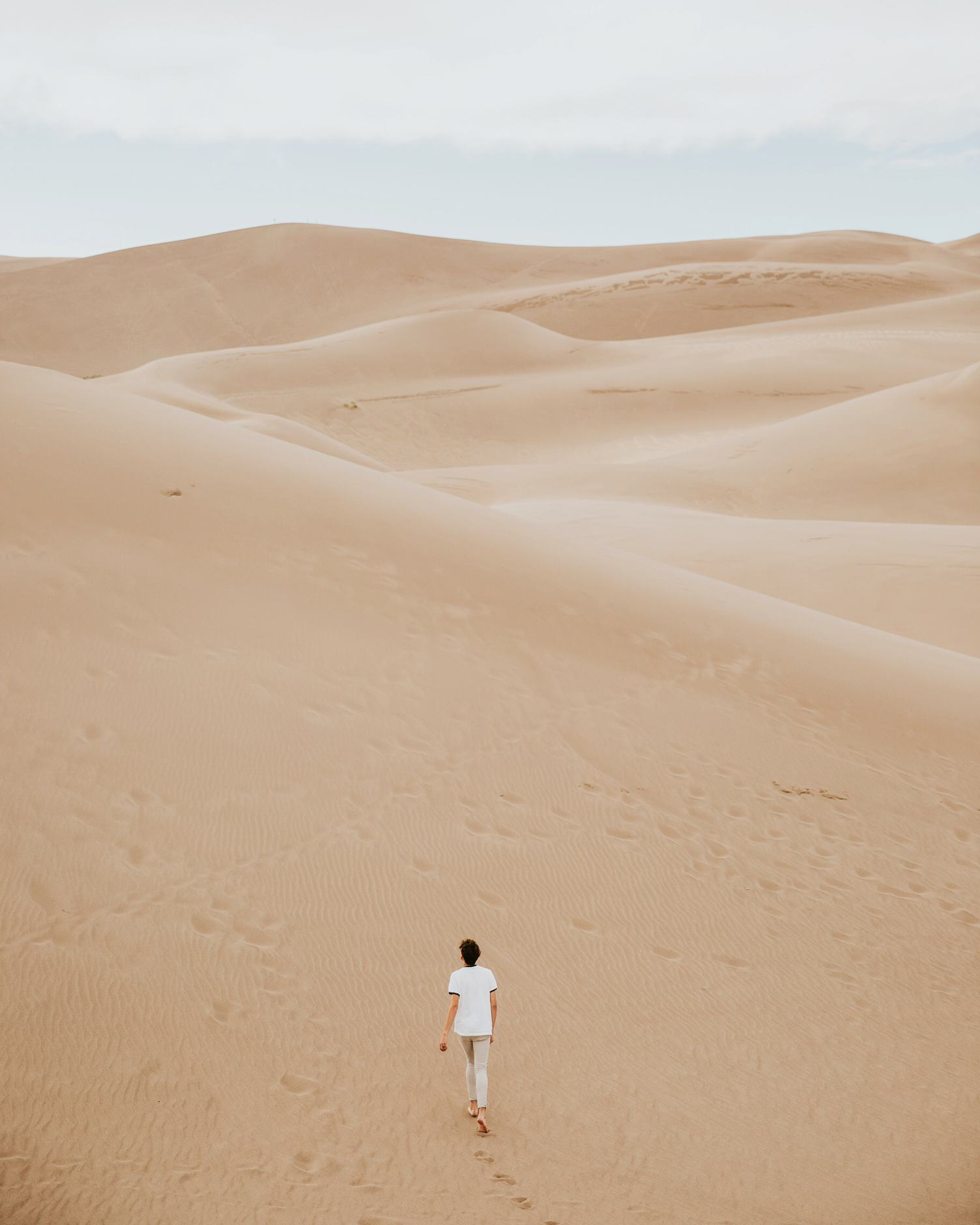 Solitary Person Walking through Sand Dunes