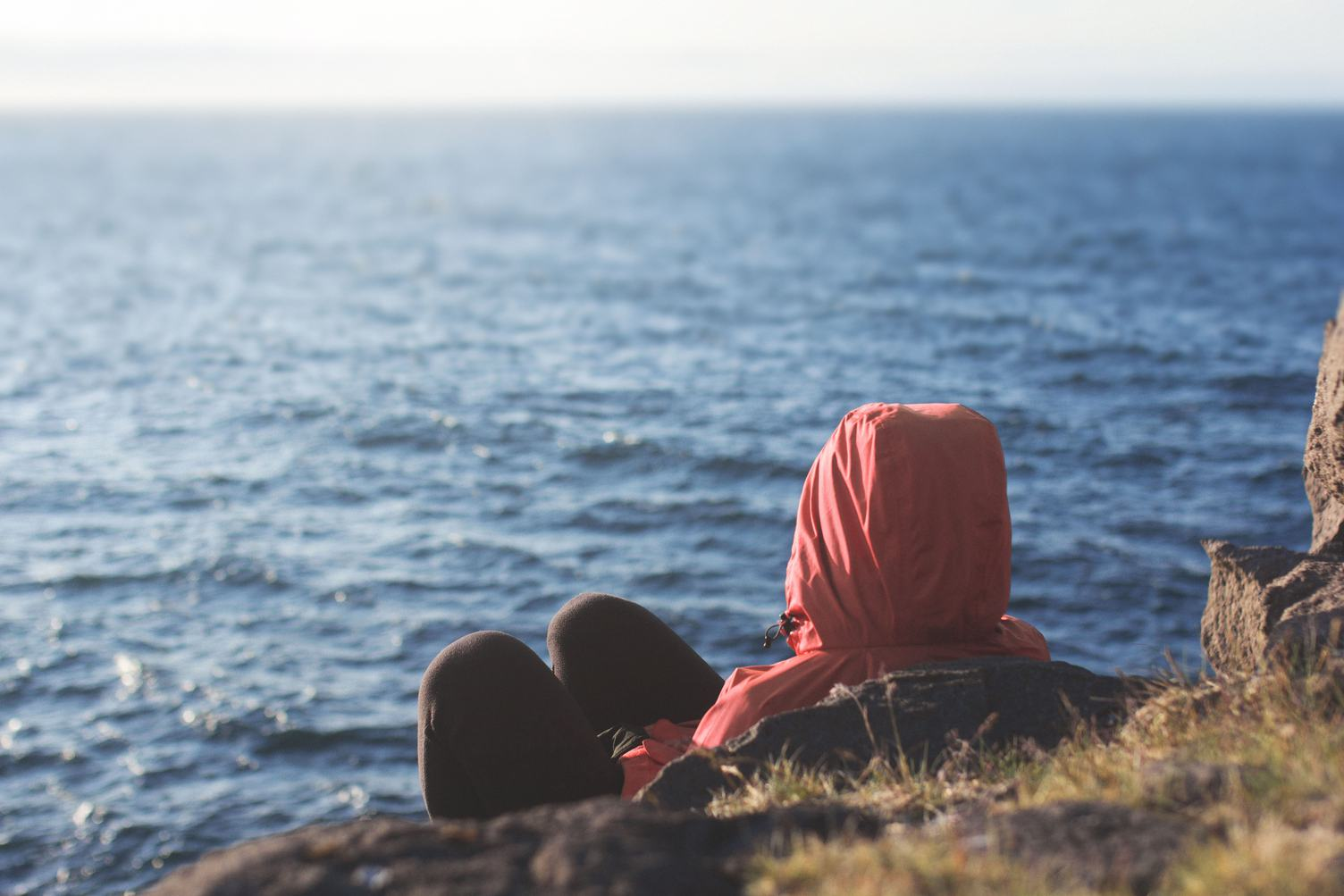 A Hooded Person Sitting on a Cliff Overseeing the Sea