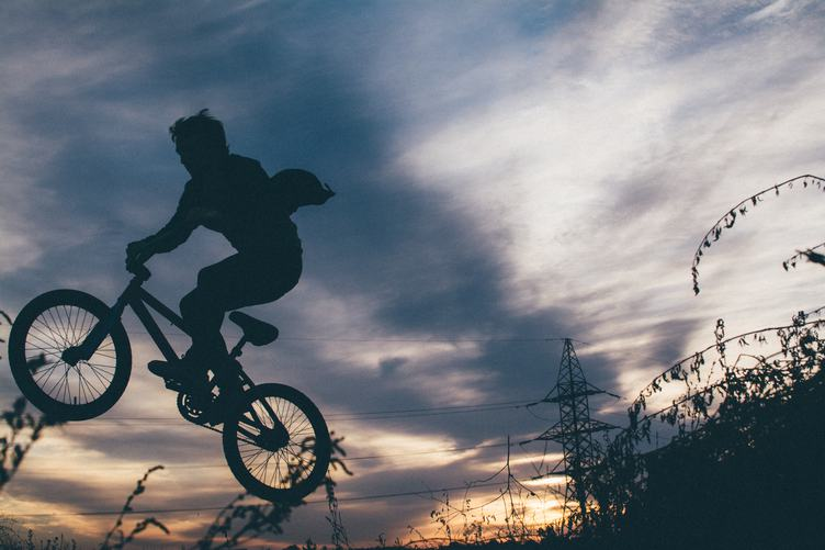 Silhouette of a Young Man Jumping on a Bike