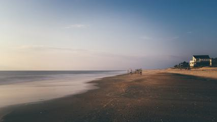 Seaside View with a Group of People Walking on Wet Sand