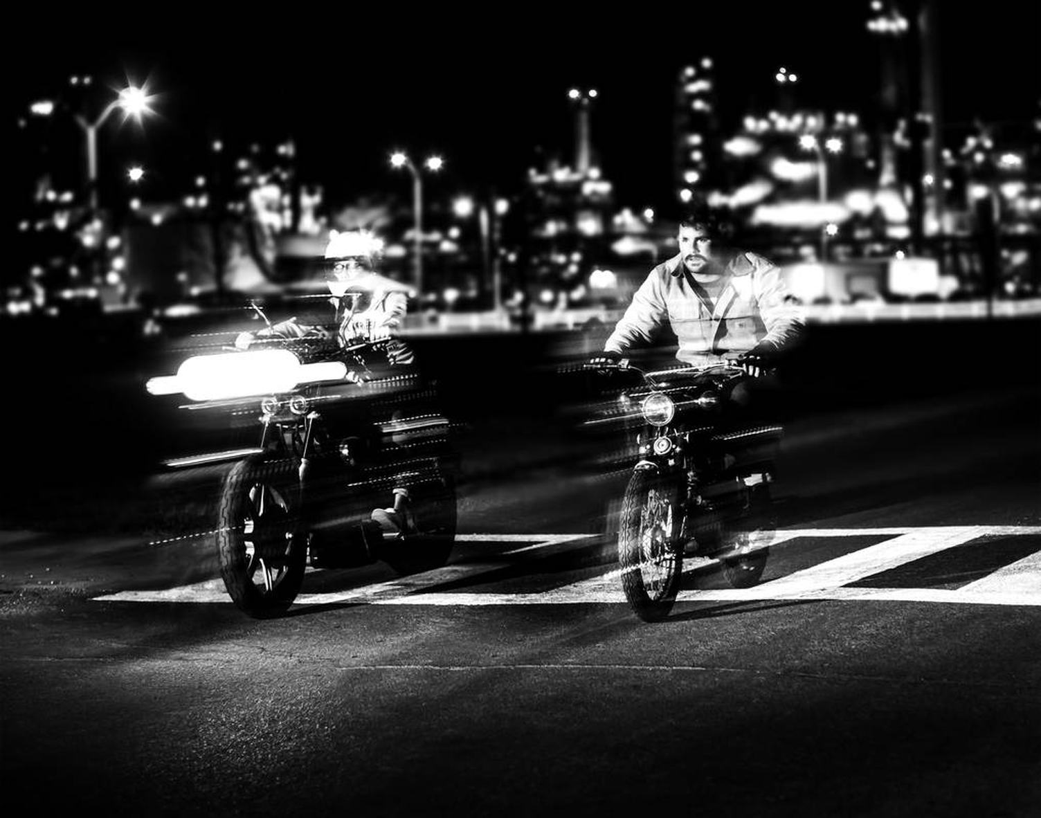 Motion of Two Bikers Racing on the Street at Night
