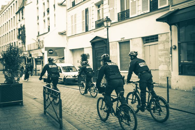Police Patrol on Bicycles in a Small City Street