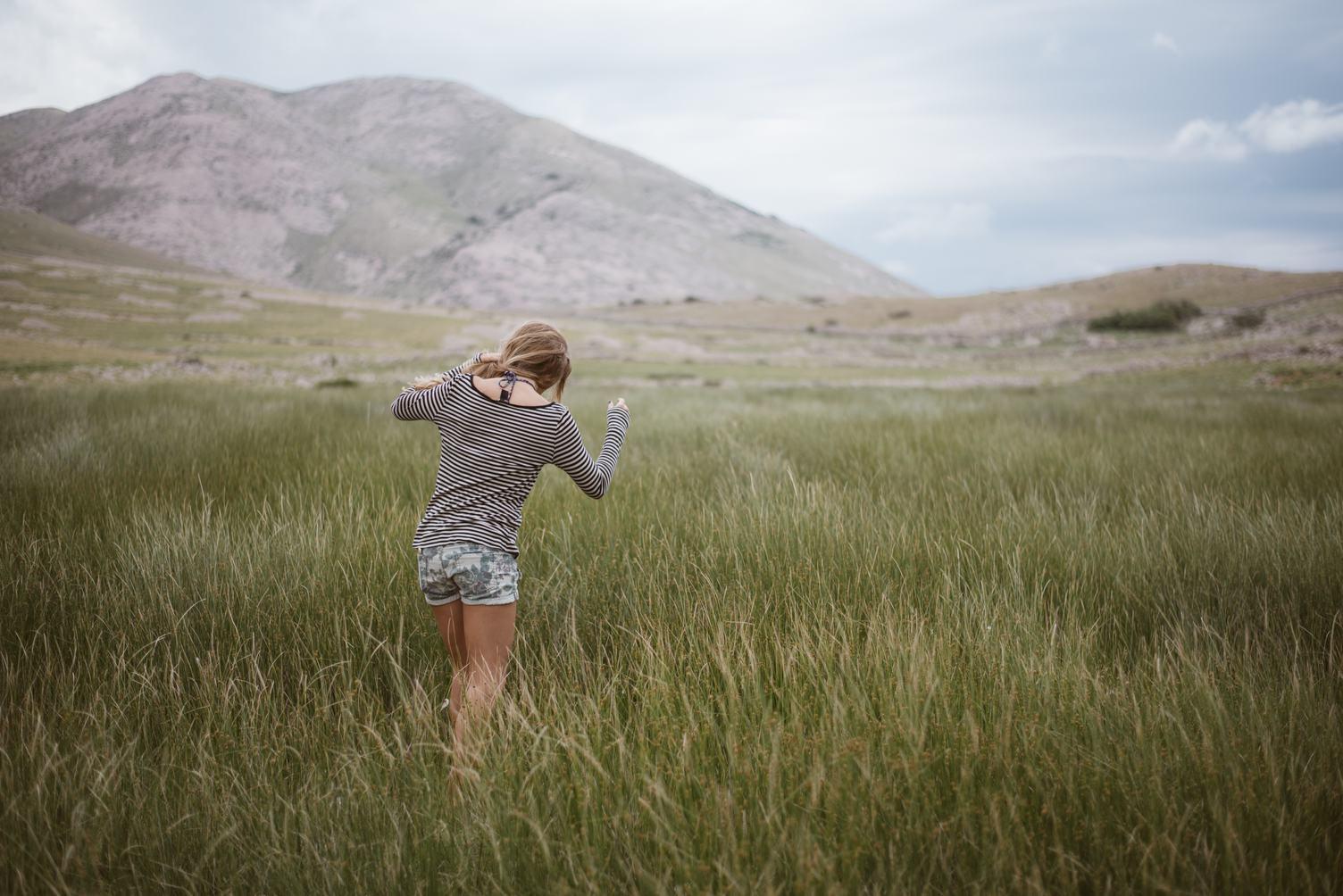Young Girl Wearing Striped Shirt Walking Through A Green Meadow