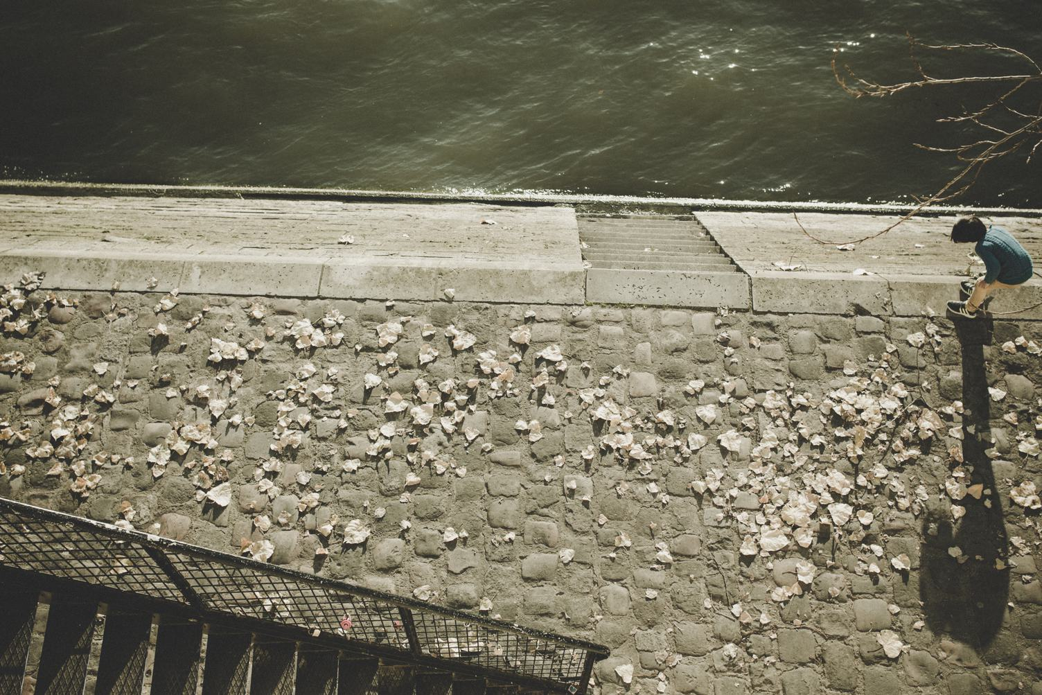 Boy Playing with Stones on the Embankment