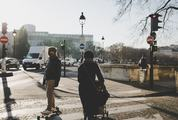 Lady with a Stroller and a Skateboarder Crossing the Street