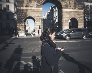 Brunette Walking the Street with a Smartphone in her Hands