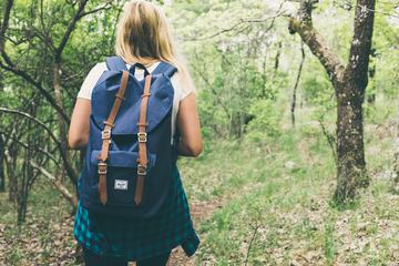 Blond Girl with a Backpack Exploring a Forest