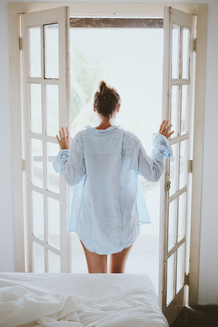 Young Woman in a Shirt Opening the Balcony Door